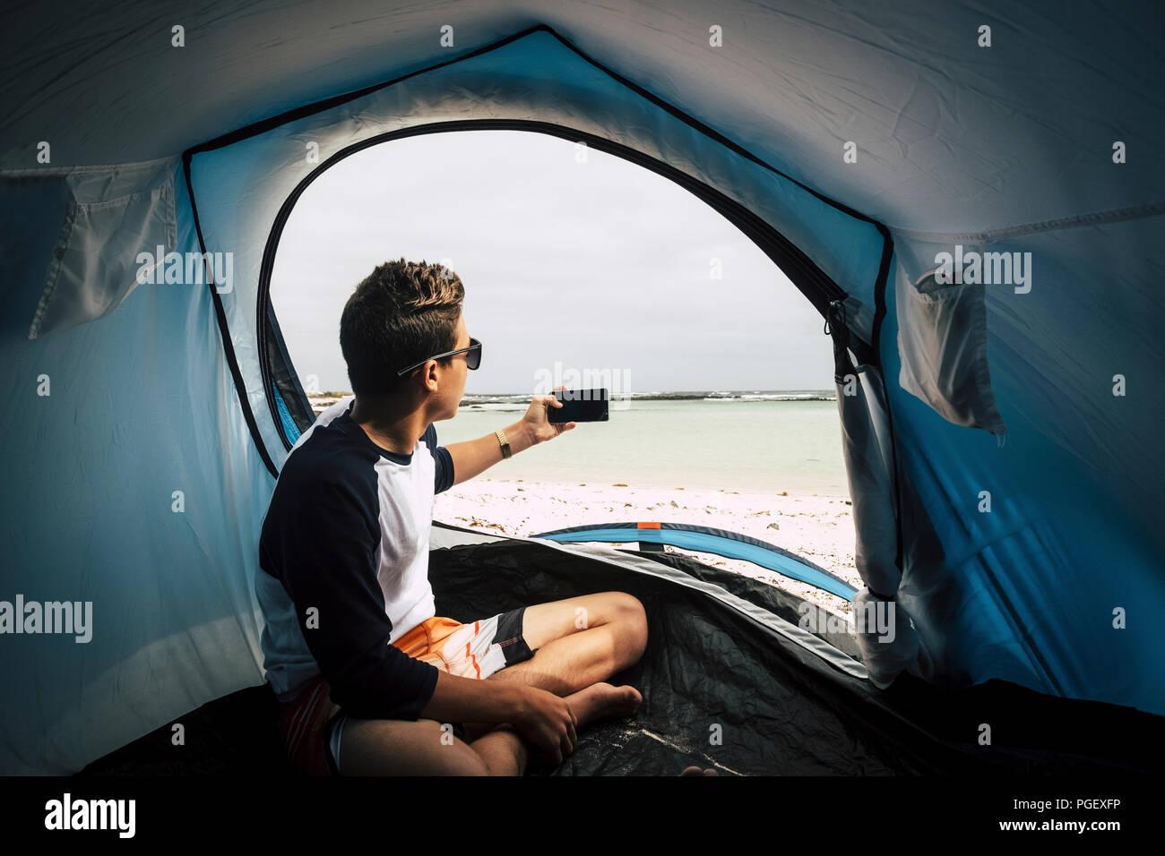 Adolescente bello ragazzo camp direttamente sulla spiaggia bianca in paradiso tropicale luogo isole. dalla porta della tenda per scattare una foto con il telefono Immagini Stock