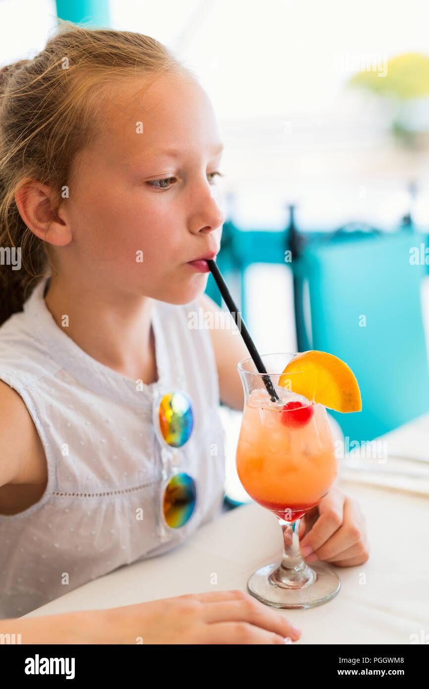 Adorabile bambina di bere succo tropicale mocktail a outdoor cafe sul giorno di estate Immagini Stock