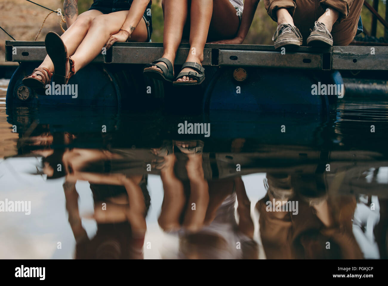 Gli amici su una vacanza seduti insieme su un bacino galleggiante in plastica barili. Gli amici seduti vicino al lago con il loro riflesso nell'acqua. Immagini Stock