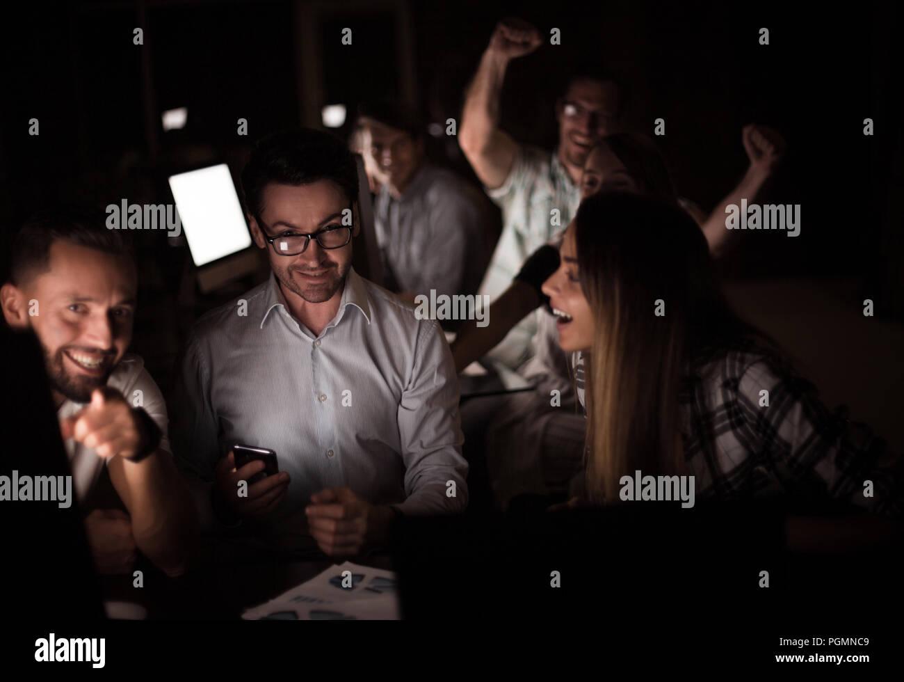 Happy business team nel luogo di lavoro di sera. Immagini Stock