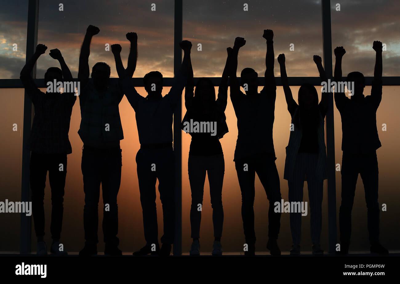 Team aziende in piedi vicino alla finestra con le mani in alto Immagini Stock