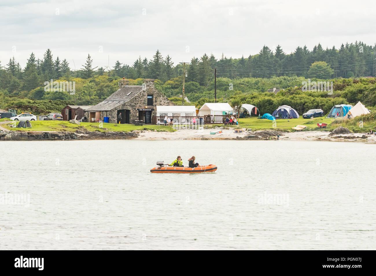 Isola di Gigha - una piccola barchetta a vela attraverso Ardminish Bay, dal Boathouse ristorante di pesce e piccolo campeggio, Argyll e le isole della Scozia, Regno Unito Immagini Stock