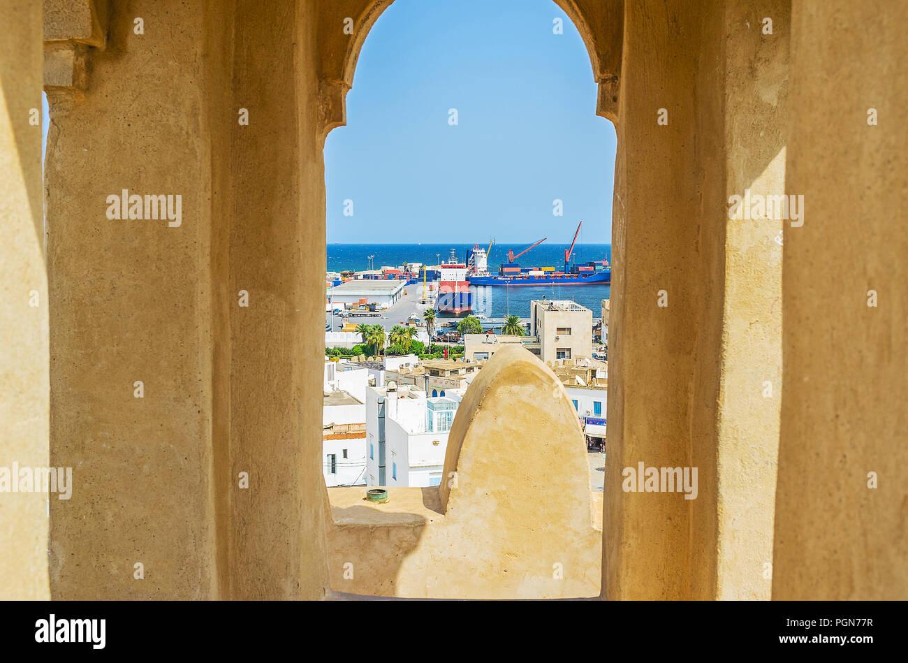 La piccola finestra nella torre della fortezza Ribat si affaccia sui tetti della Medina e porto industriale, Sousse, Tunisia. Immagini Stock