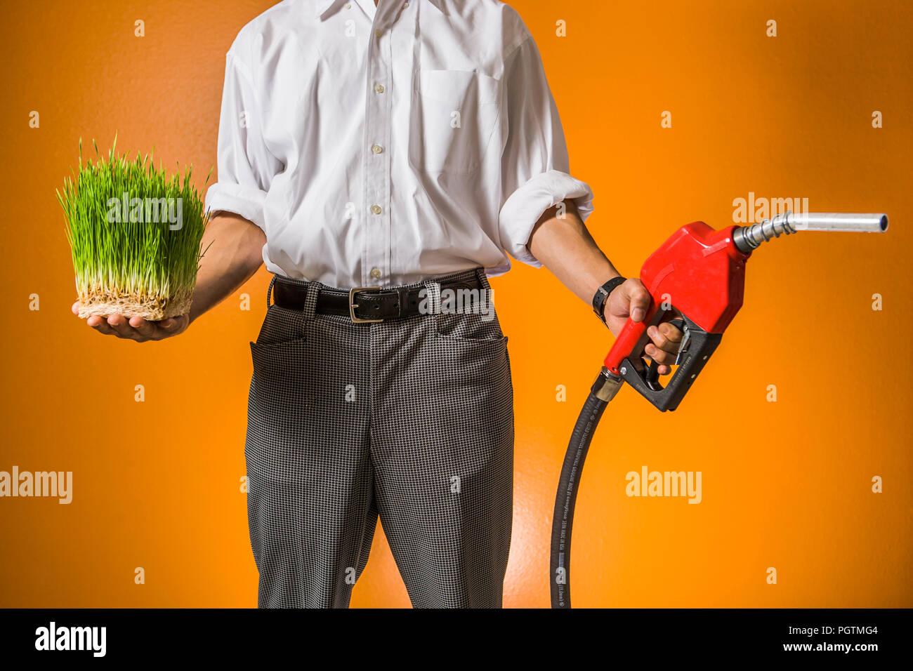 Un uomo con un piatto di erba di frumento in una mano e un ugello di benzina nell'altro. Concetto di combustibili verdi vs combustibili fossili. Immagini Stock