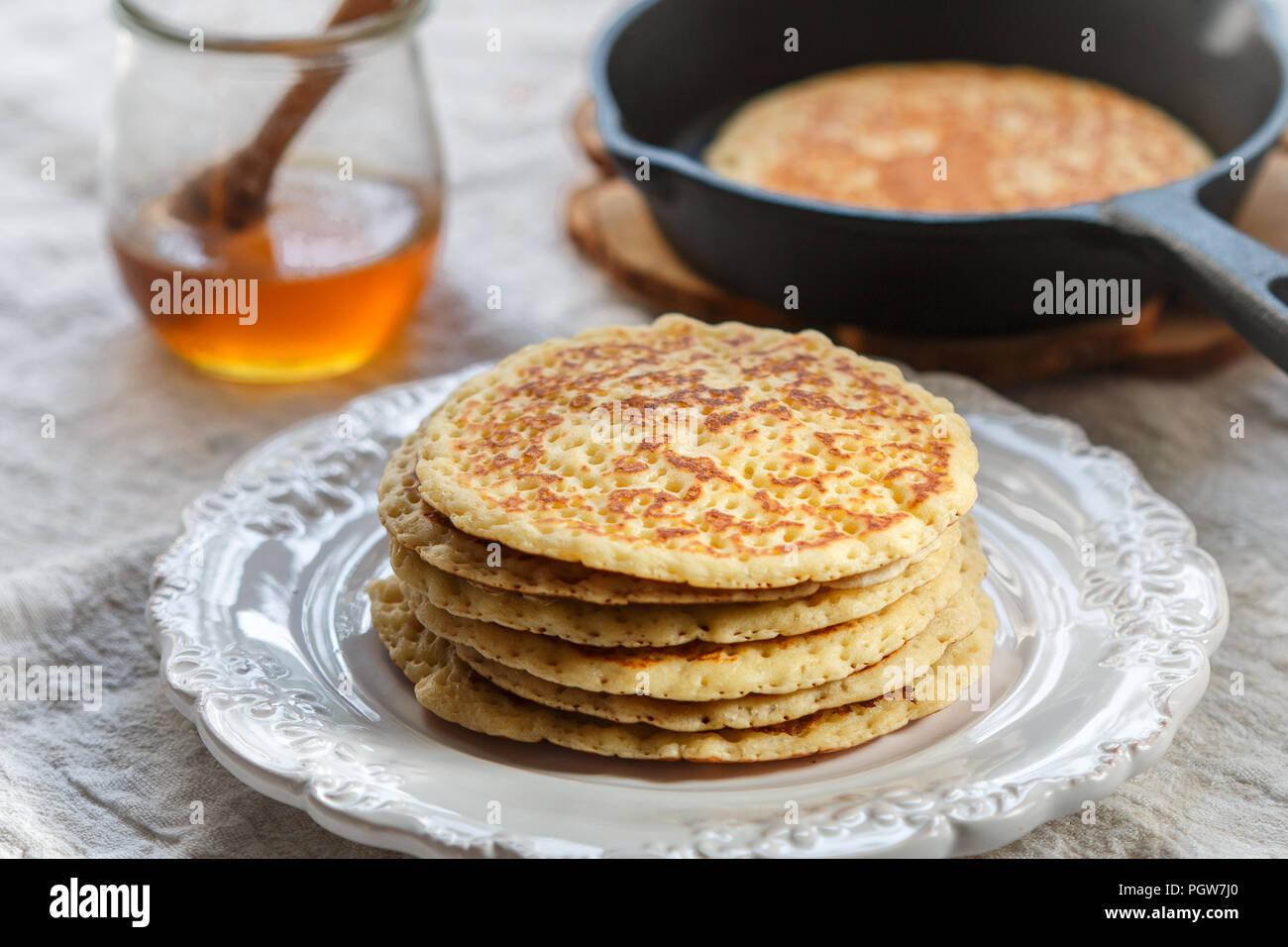 Deliziosi dolci American frittelle con miele su una piastra bianca. La prima colazione è gourmet. Messa a fuoco selettiva Immagini Stock