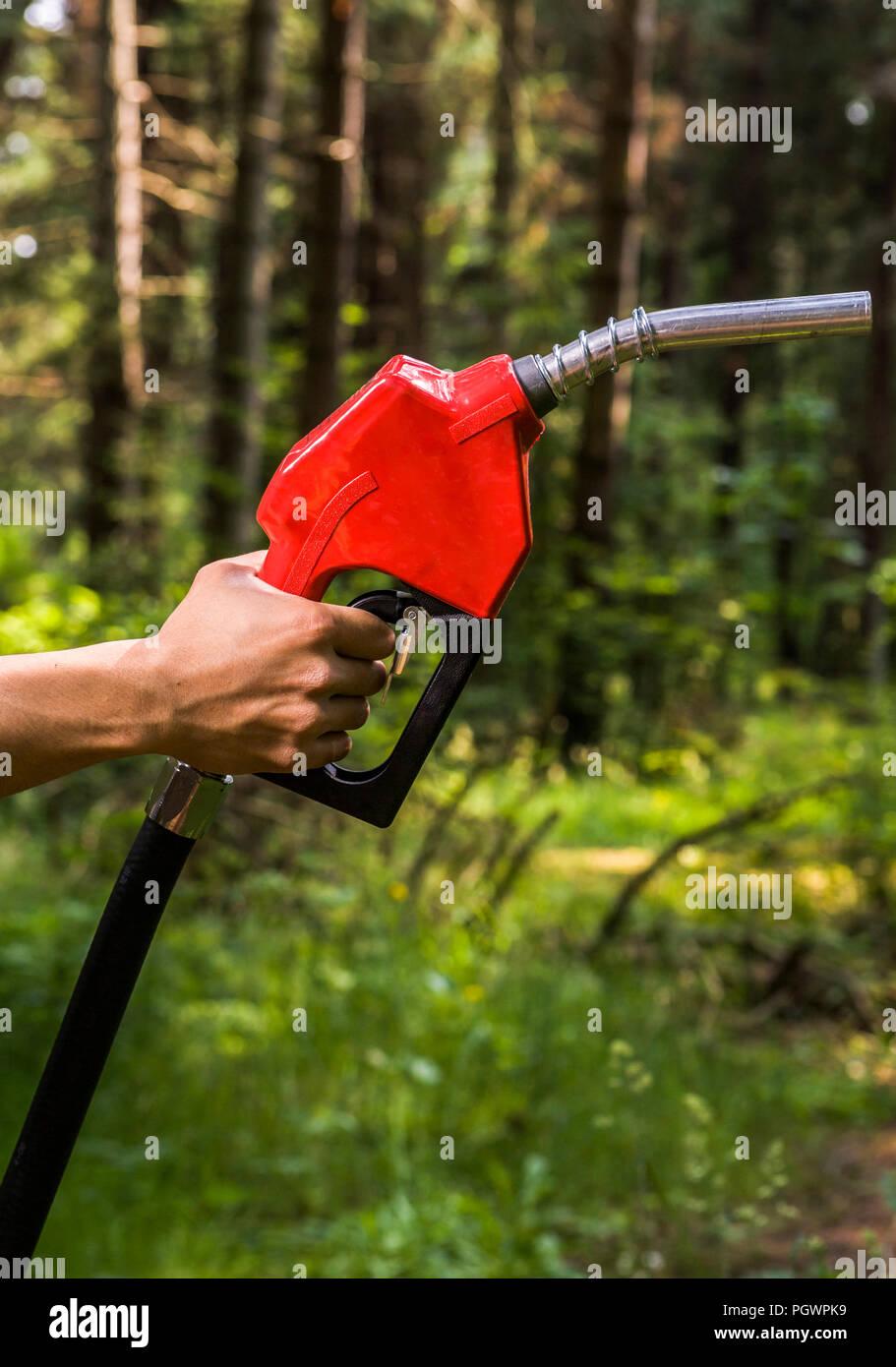 La mano di una persona in possesso di una pompa di benzina ugello in una foresta impostazione. Concetto, questioni ambientali attorno al petrolio. Immagini Stock
