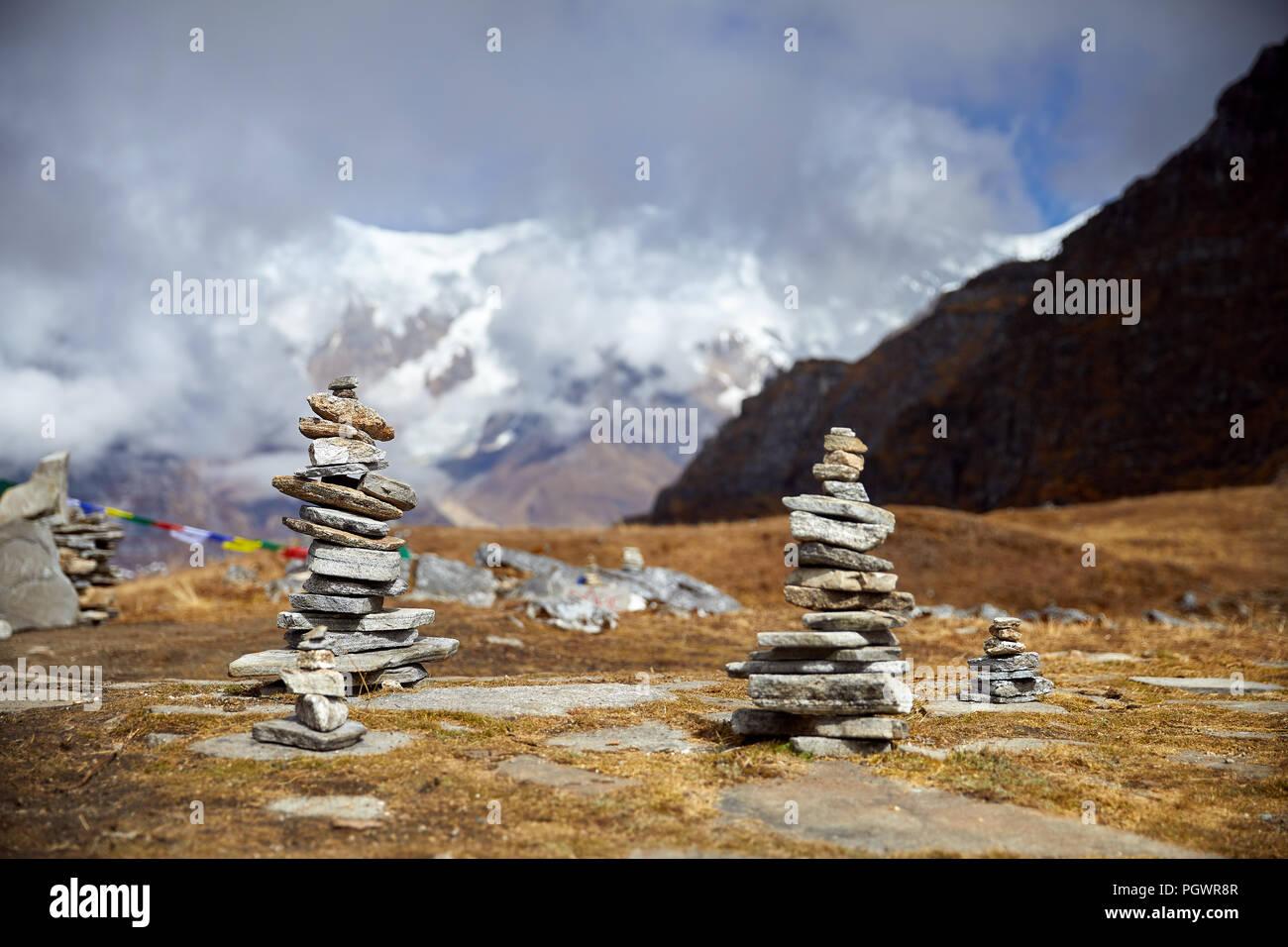 Piccoli mucchi di pietre sul Mardi Himal trek e nuvoloso cime delle montagne dell Himalaya in Nepal Immagini Stock