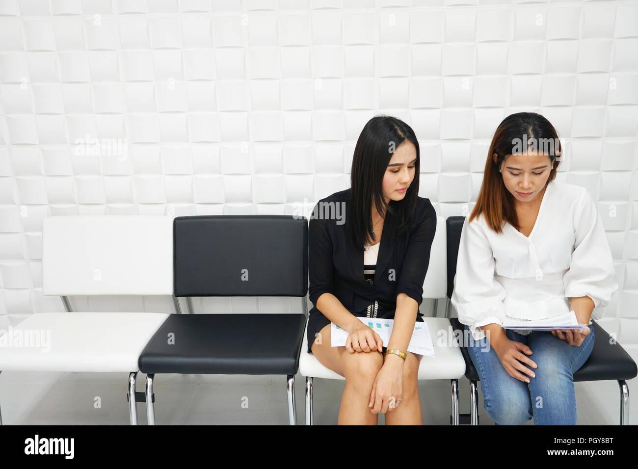 Due donne aspettano per i tempi di attesa per un colloquio. Foto Stock