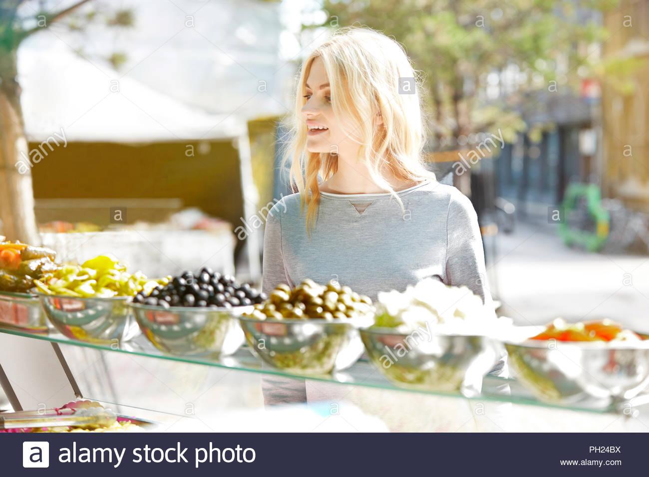 Giovane donna shopping presso snack stand. Immagini Stock