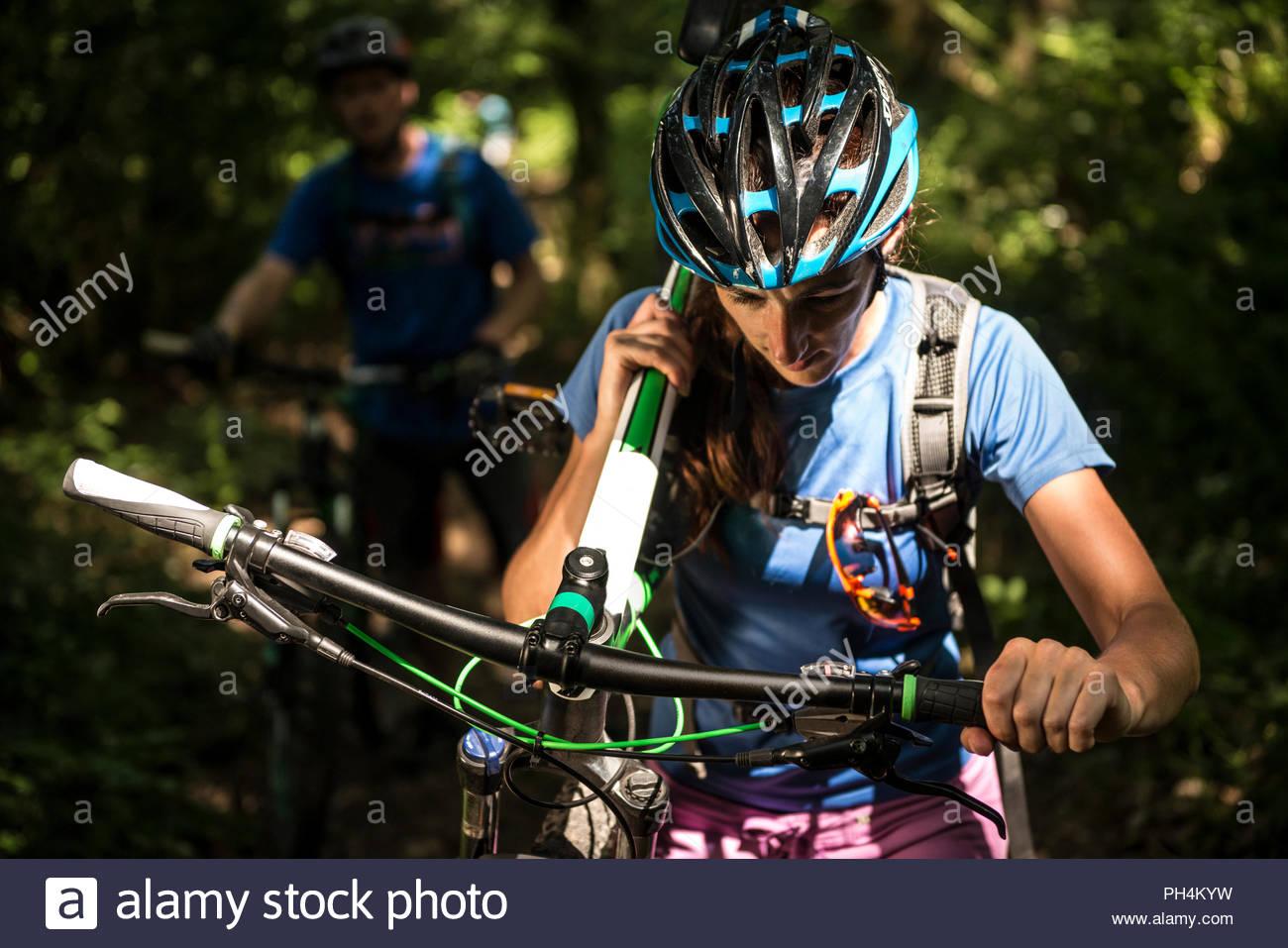 Donna che trasportano mountain bike nella Foresta Immagini Stock