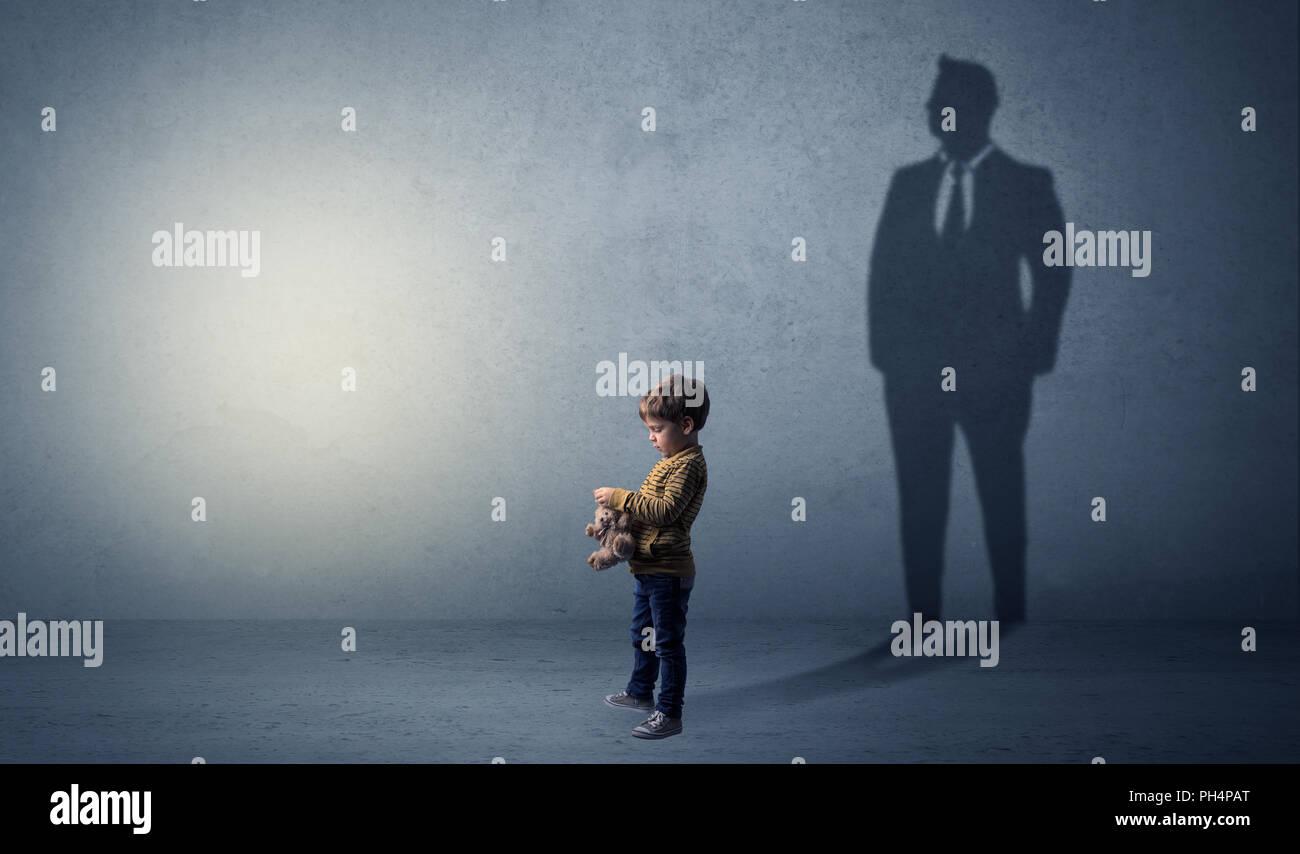 Little Boy immaginare che egli sarà uomo d affari e illustrando il suo futuro in una grande ombra Immagini Stock