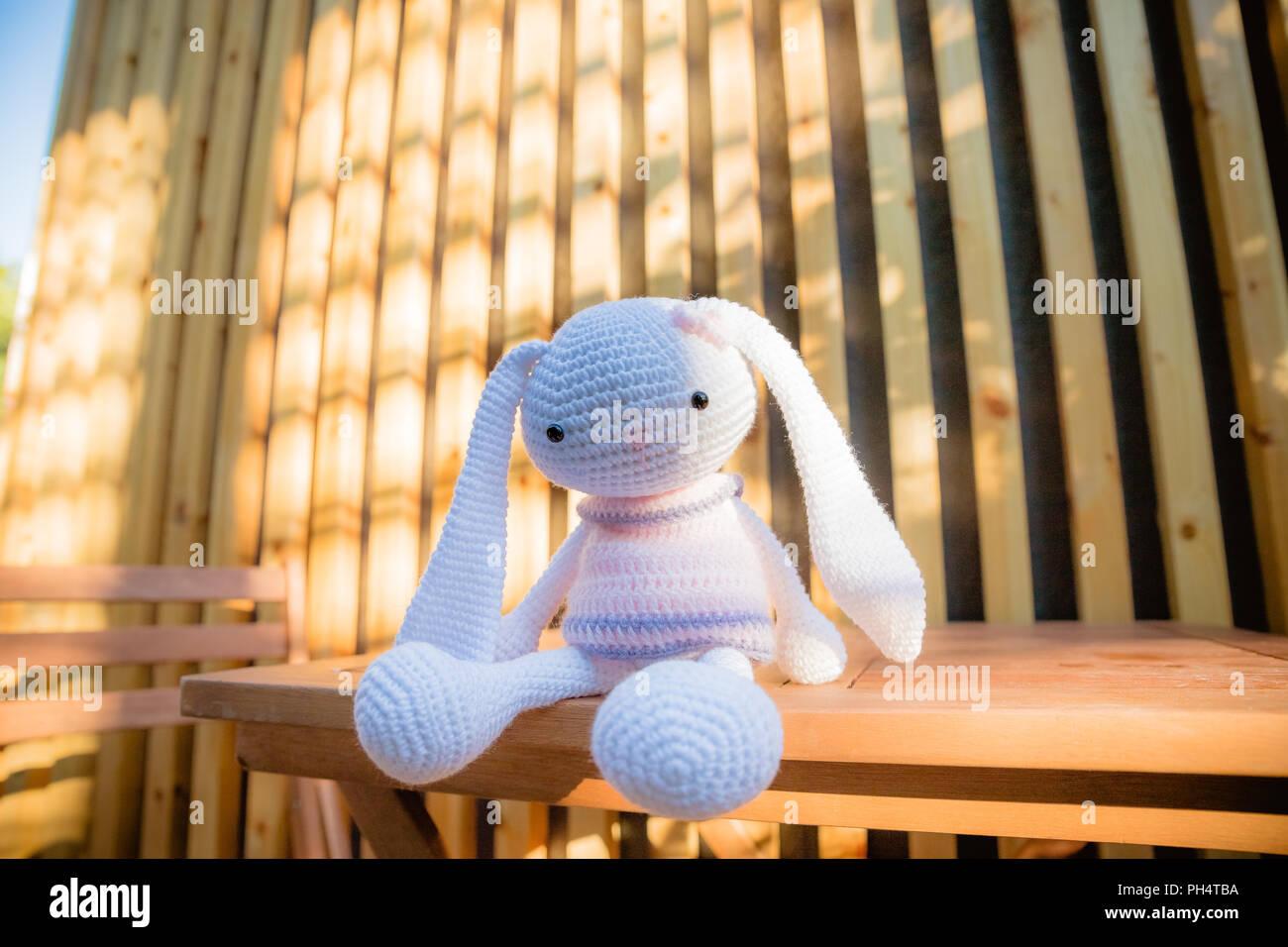 Un Piccolo Maglia Coniglio Bianco In Un Abito Rosa Sul Tavolo Di Legno Giocattolo A Maglia Fatte A Mano Di Cucito Carino Bunny Con Le Orecchie Lunghe Coniglietto A Maglia Festive Decor Il