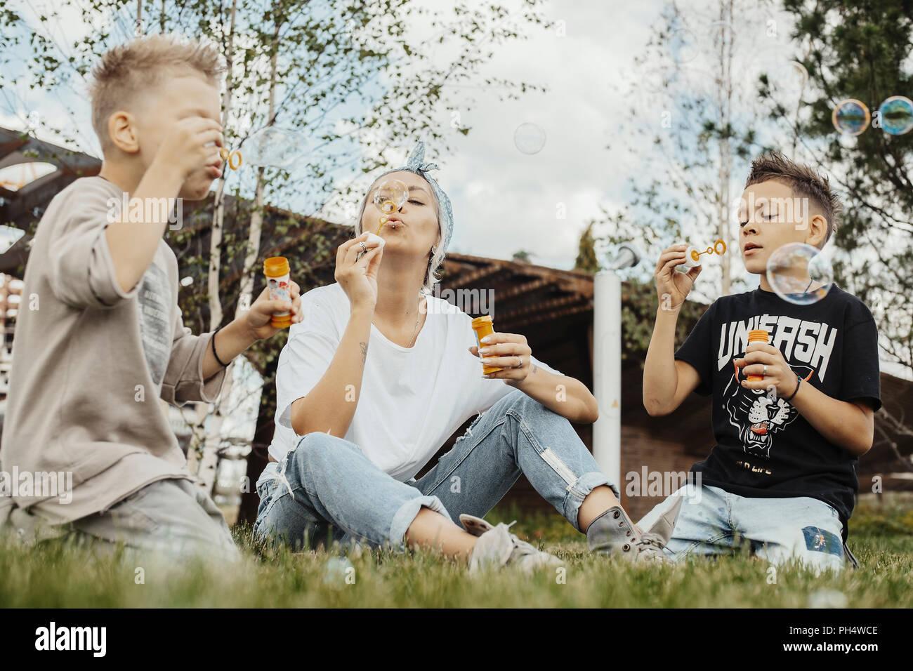 Close up della famiglia soffiare bolle all'aperto nel parco. Immagini Stock