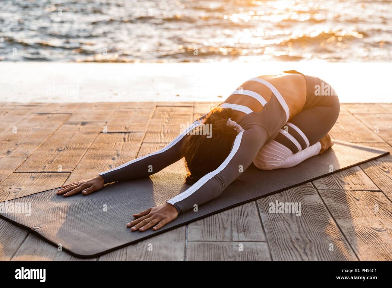 Immagine di incredibile forte giovane donna fitness all'aperto in spiaggia fare yoga esercizi di stretching. Immagini Stock