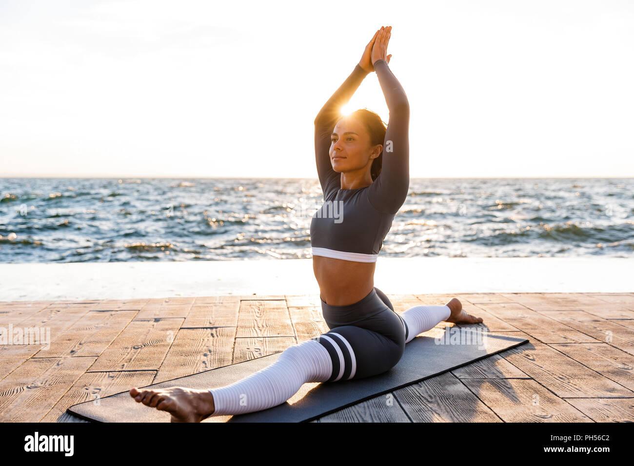 Immagine di concentrato di giovane donna fitness all'aperto in spiaggia fare yoga esercizi di stretching. Immagini Stock