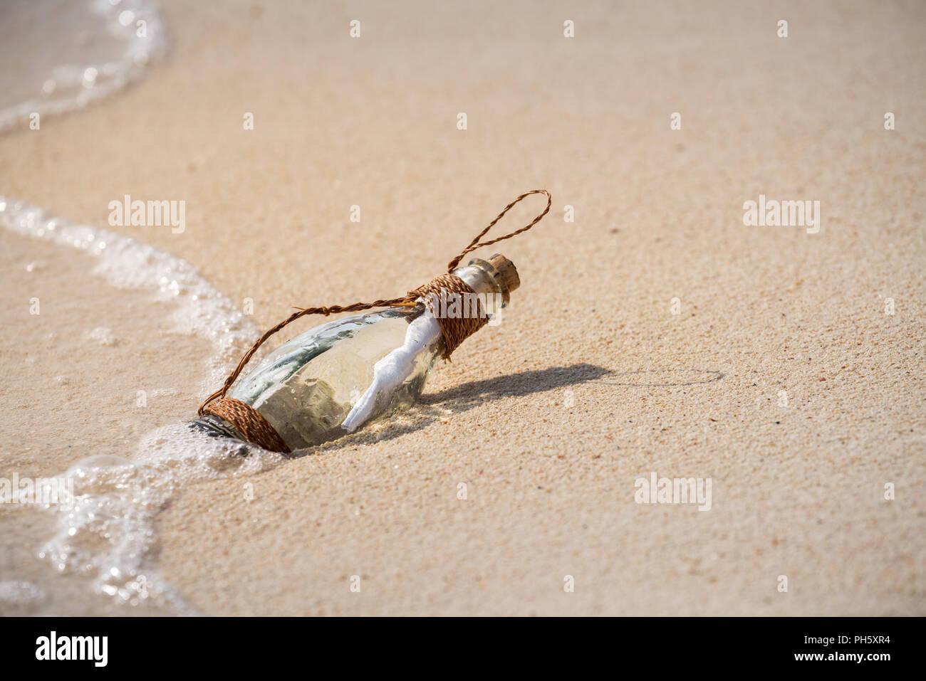 Lettera messaggio in un bicchiere bottiglia trasparente sulla spiaggia , concept per la comunicazione. Immagini Stock