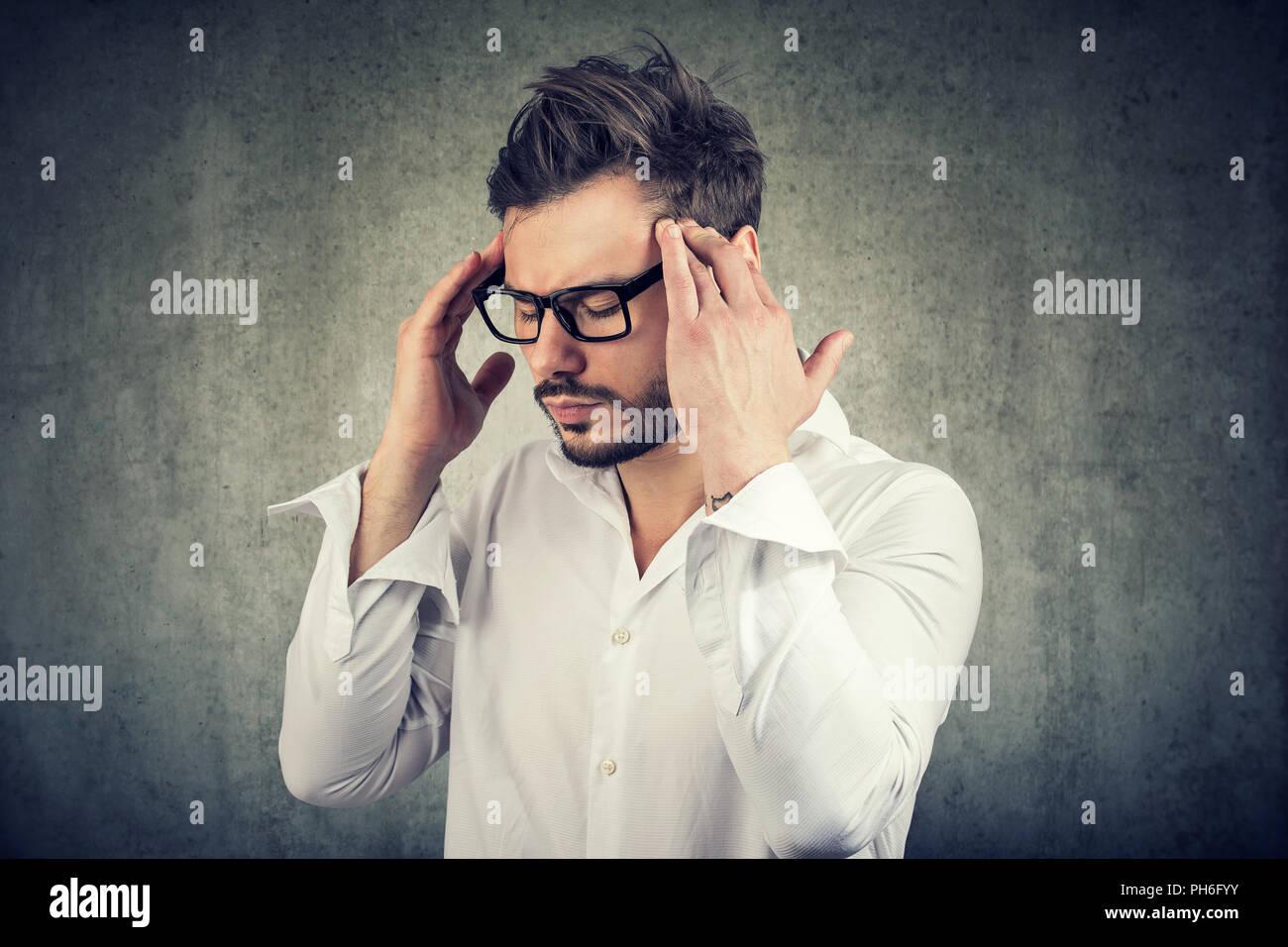 Uomo adulto in bicchieri tenendo le dita sulle tempie cercando di concentrarsi sul processo decisionale Immagini Stock