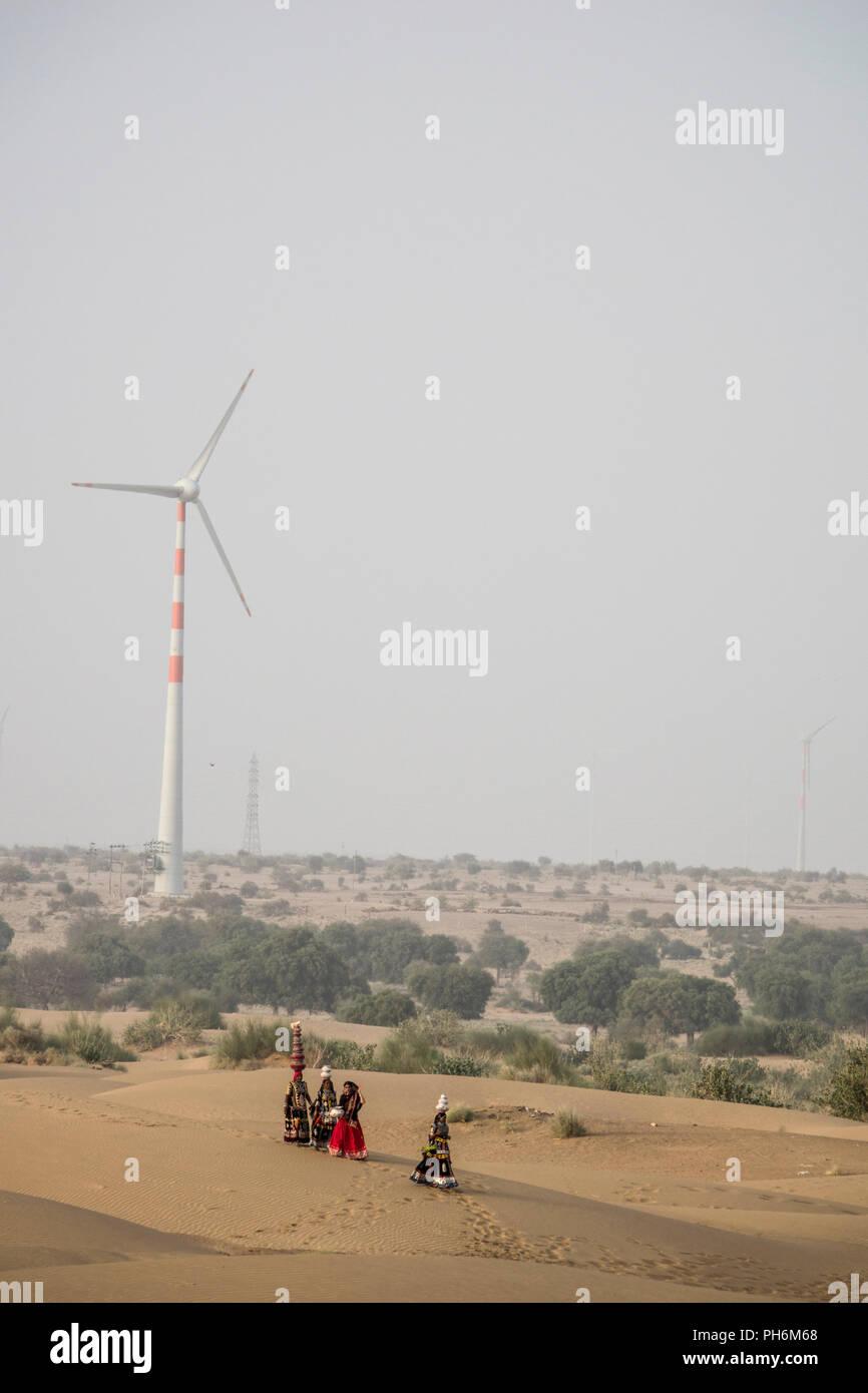 Le donne nomadi del deserto di Thar con turbina eolica in background, Rajasthan, India Immagini Stock