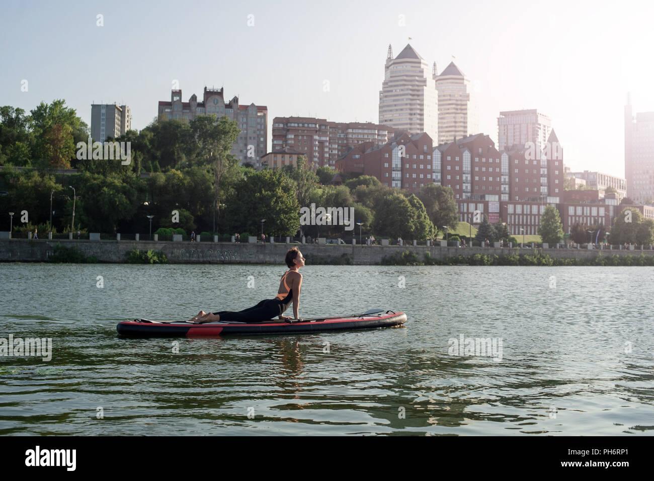 Lo yoga sul sup board, silhouette di donna sulla spiaggia Immagini Stock