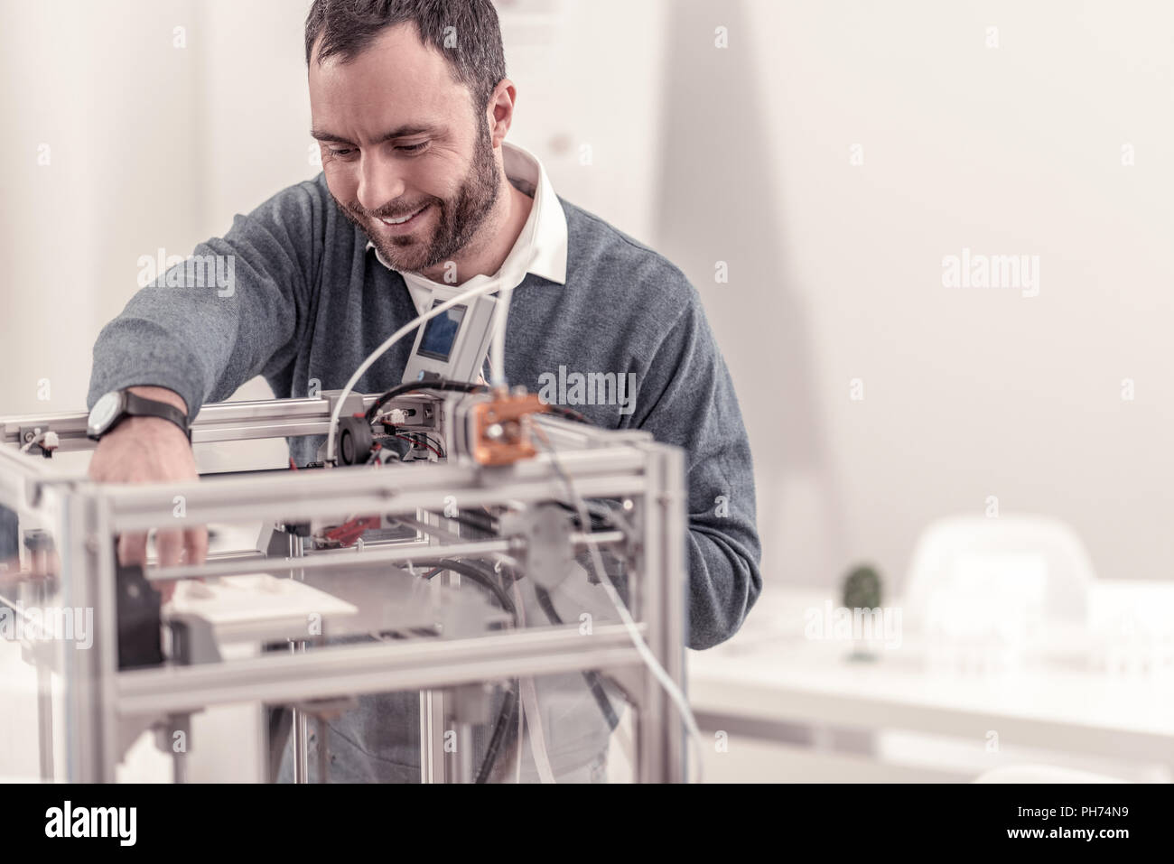 Sorridente uomo adulto alla sperimentazione di nuove a3D printer Immagini Stock