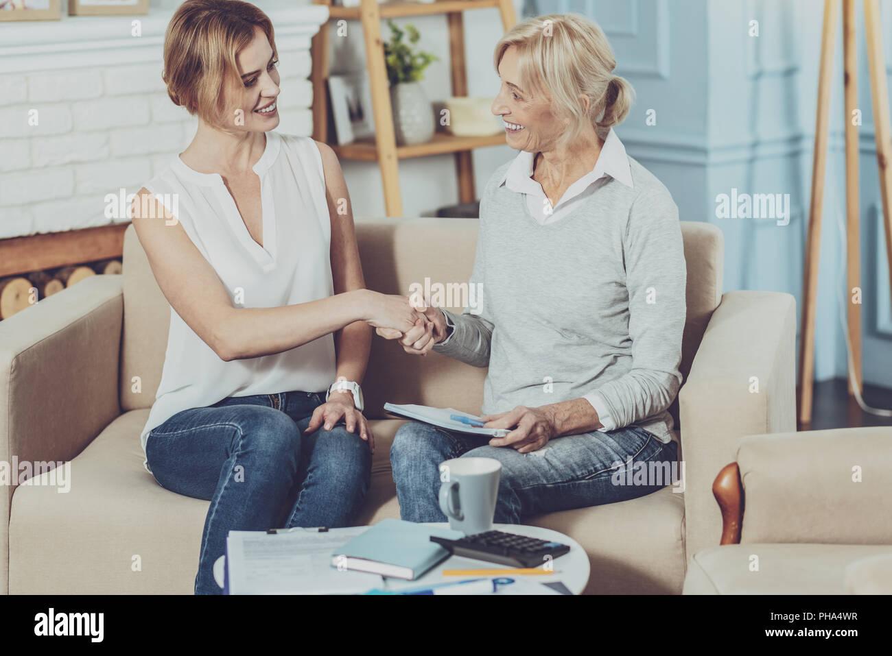 Positivo donna invecchiato saluto il suo consulente finanziario Immagini Stock