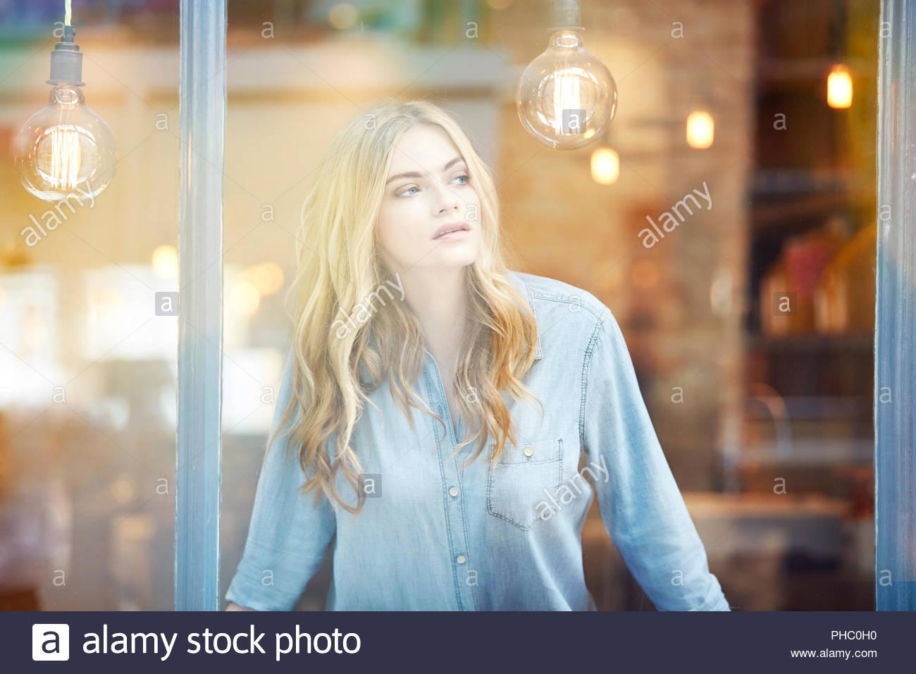 Giovane donna a guardare fuori dalla finestra. Immagini Stock