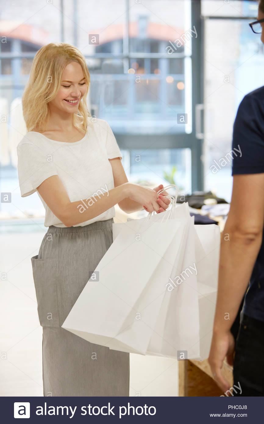 Sorridente giovane donna azienda borse per lo shopping. Foto Stock