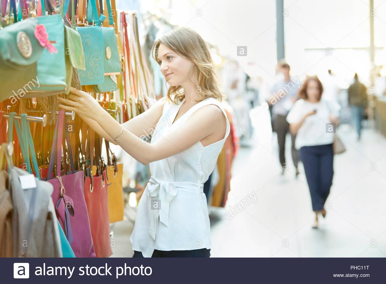 Giovane donna shopping per borsetta a street market. Immagini Stock
