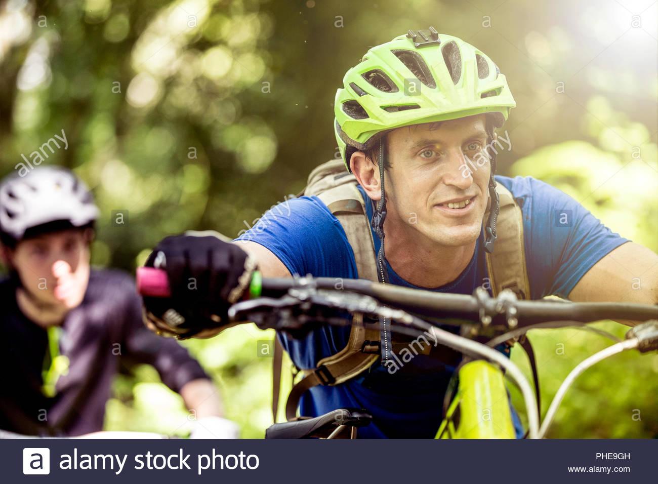 L'uomo spingendo in mountain bike nella Foresta Immagini Stock
