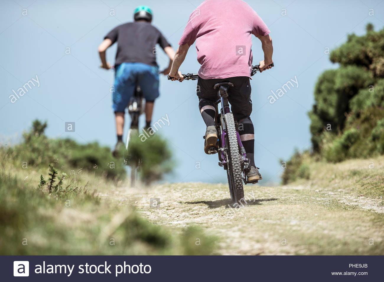 Gli uomini mountain bike in Porlock Weir, Inghilterra Immagini Stock