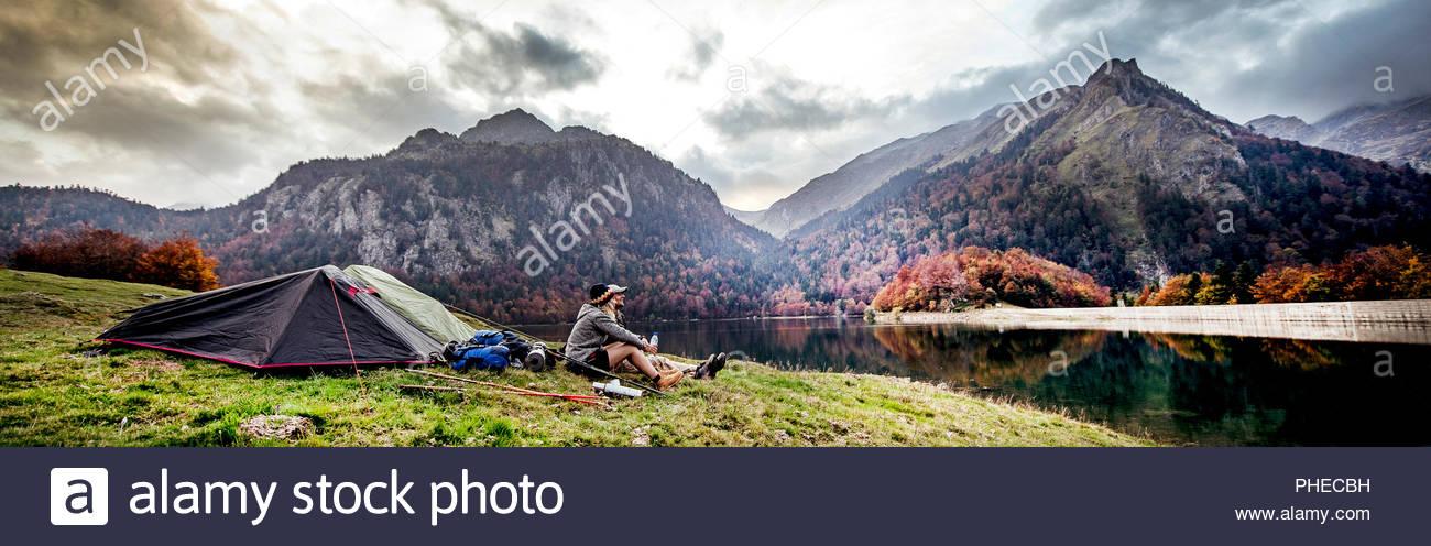 Coppia giovane in appoggio a camp accanto a montagne Immagini Stock