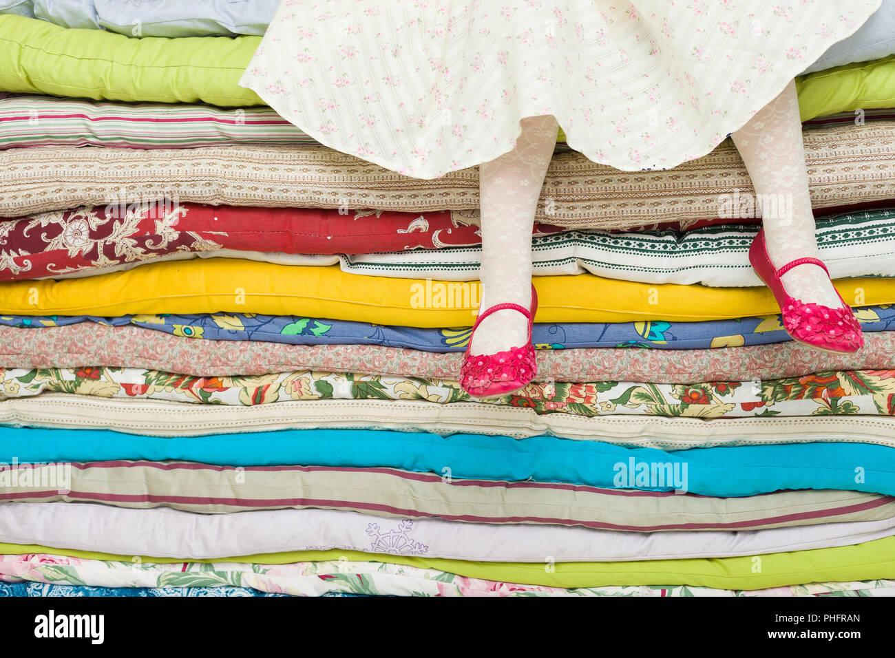 Materassi Colorati.Le Gambe Di Una Bambina Seduta Su Una Pila Di Materassi Colorati