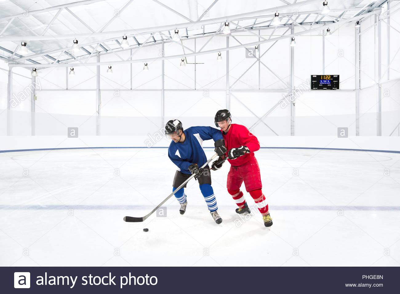 Giovani uomini in concorrenza nel corso di hockey su ghiaccio Immagini Stock