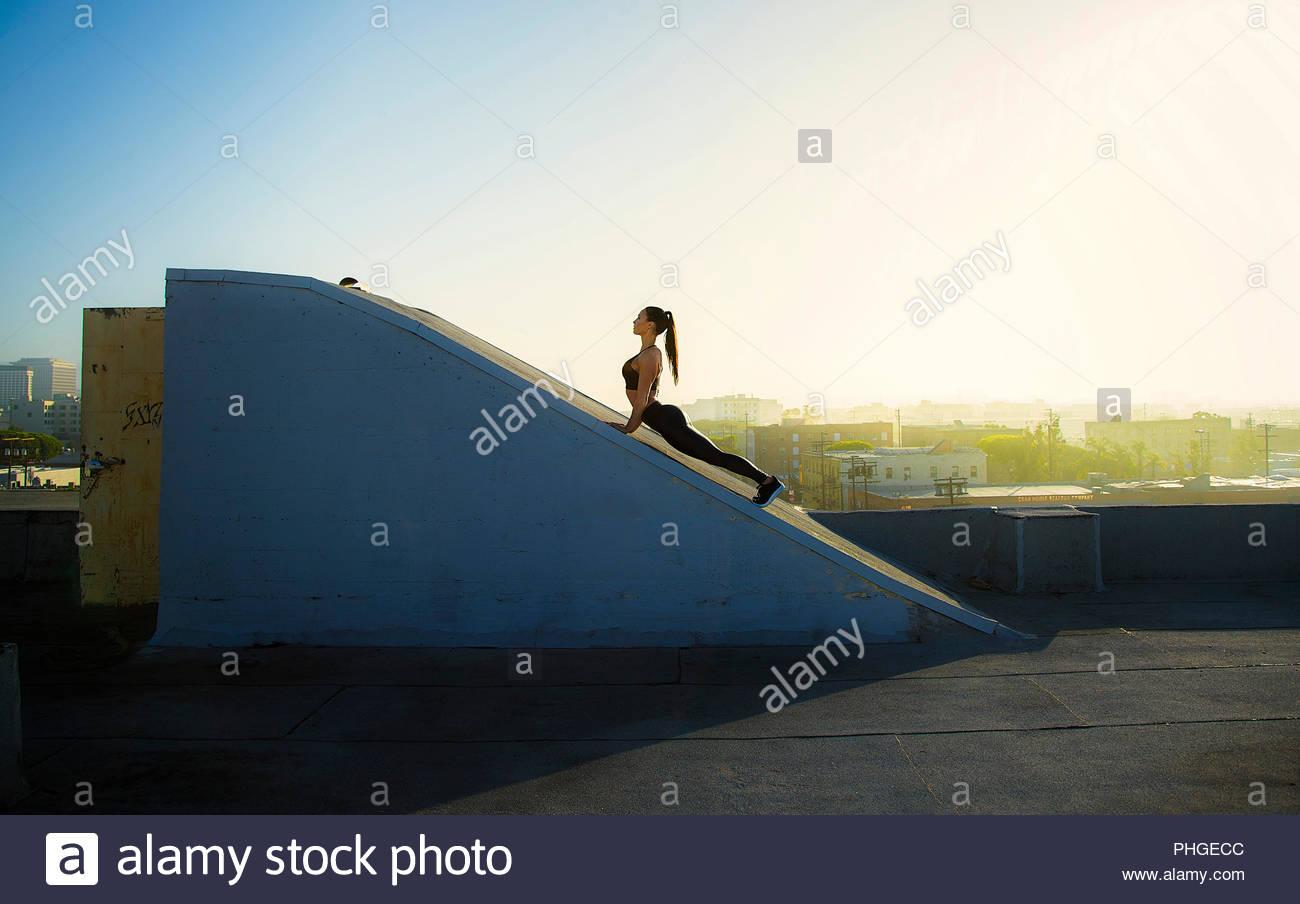 Giovane donna stiramento sulla rampa sul tetto Immagini Stock