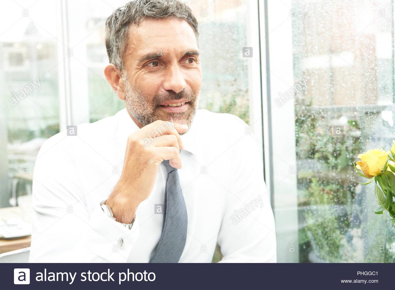 Imprenditore dalla finestra durante la riunione Immagini Stock