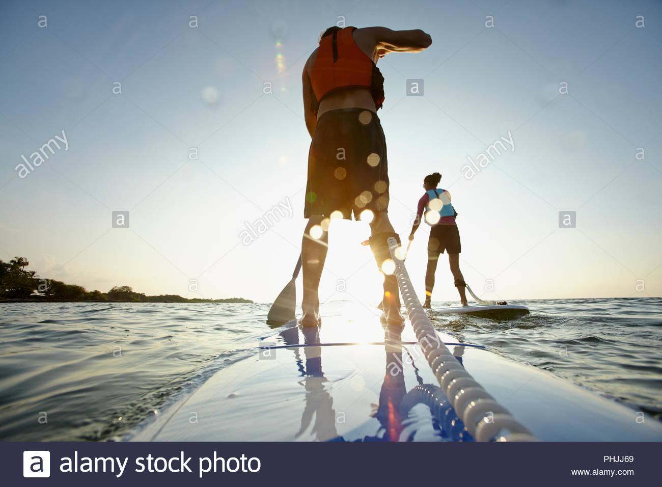 Coppia giovane paddleboarding Immagini Stock