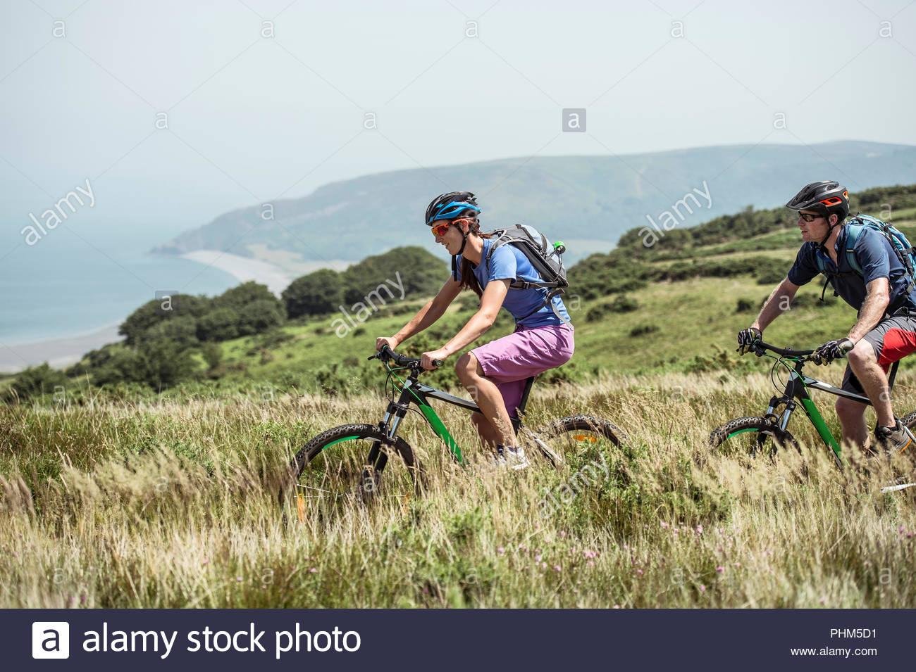 Matura in mountain bike sulla collina di Porlock Weir, Inghilterra Immagini Stock