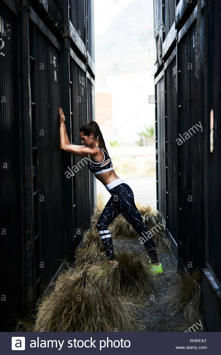 Donna che indossa abbigliamento sportivo dal contenitore di carico Immagini Stock