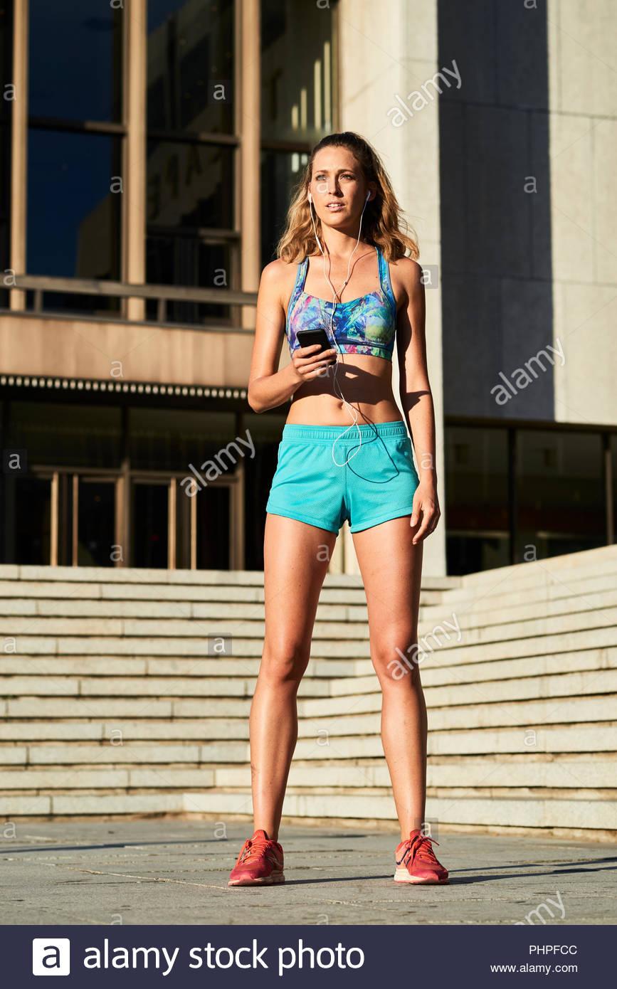 Donna che indossa abbigliamento sportivo di ascolto di musica Immagini Stock