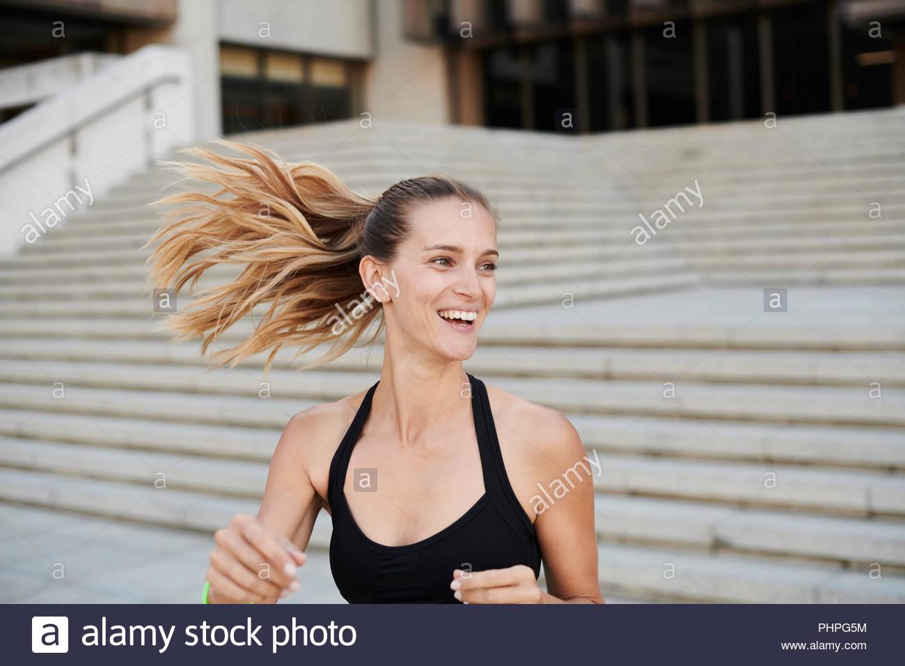 Donna sorridente con capelli spazzate dal vento Immagini Stock