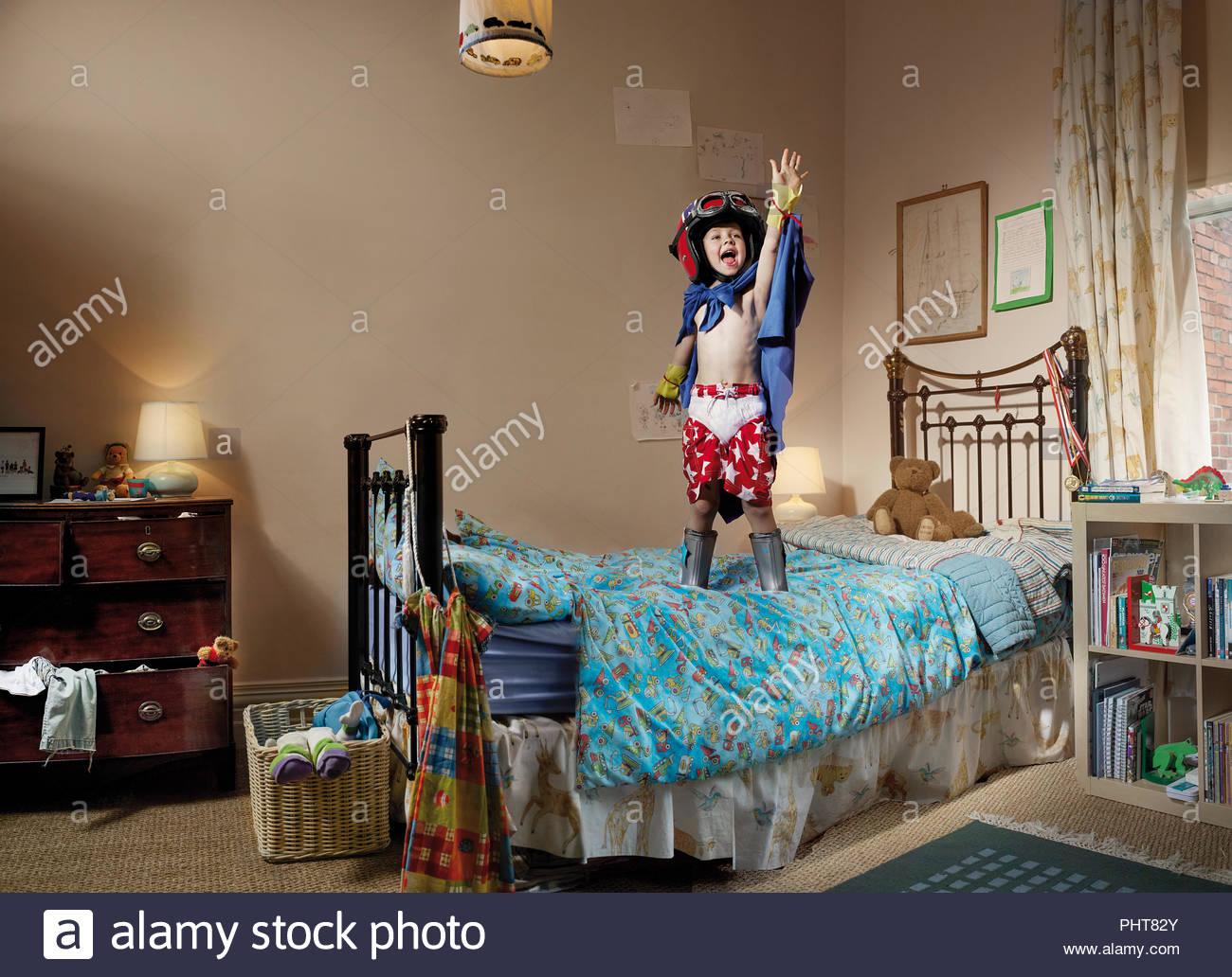Giovane ragazzo giocando sul letto Immagini Stock