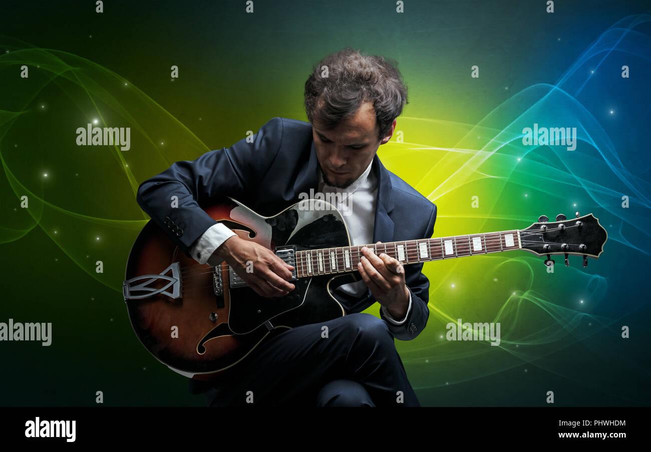 Grave chitarrista classico con il leggendario sfondo spumanti Immagini Stock