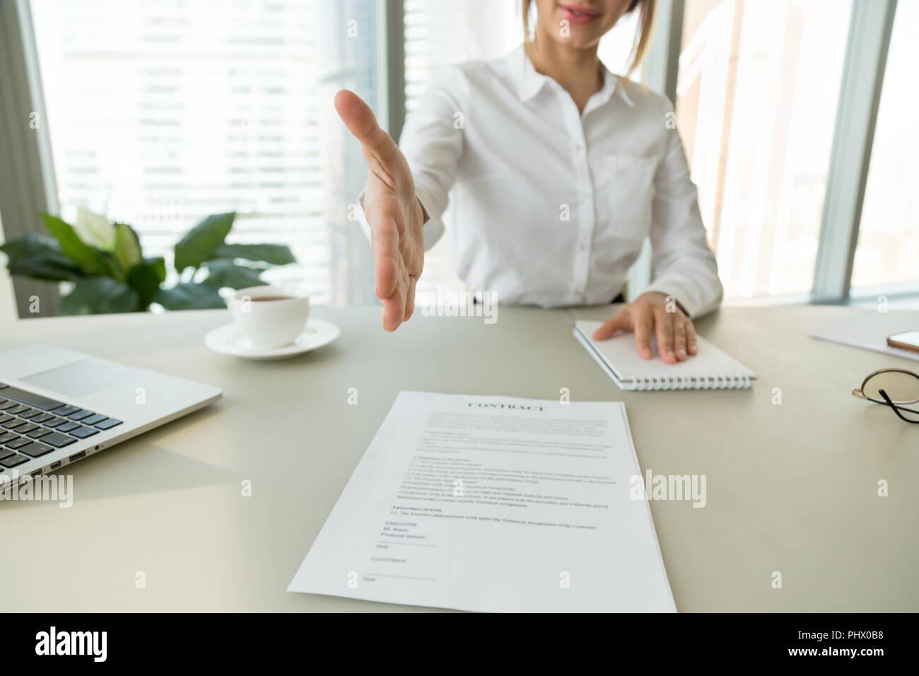 Imprenditrice datore di lavoro che si estende invece per offerta di handshake sig Immagini Stock