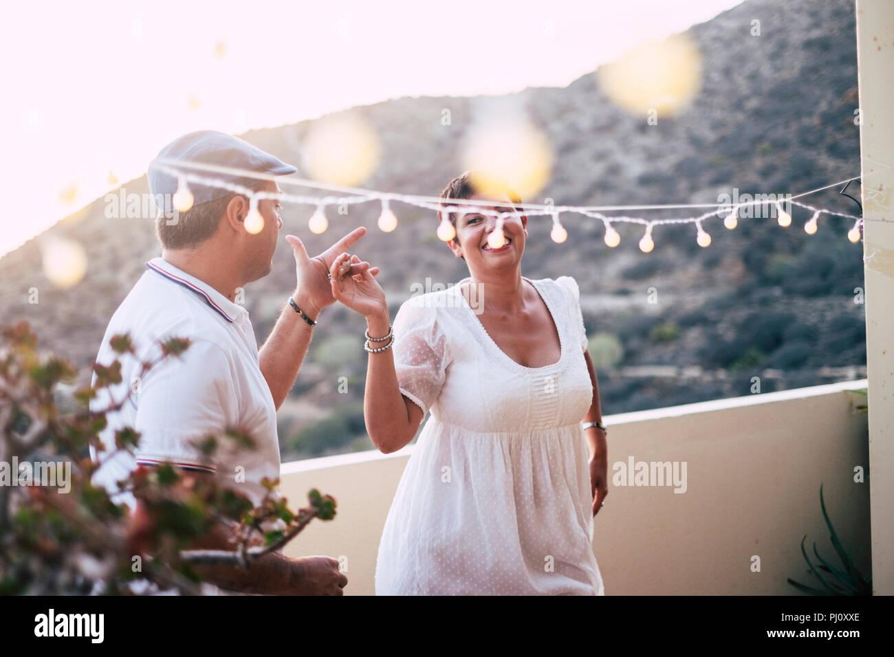 Felice caucasian persone che ballano insieme a casa in terrazza con luci durante il tramonto. romantico e il rapporto di concetto di immagine per le persone felici in Immagini Stock