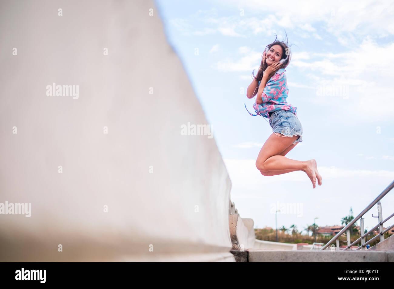 Concetto di felicità con la giovane bella ragazza jumping con gioiosa contro un cielo bianco sfondo blu. lato mare luogo. Allegra donna caucasica un sorriso Immagini Stock