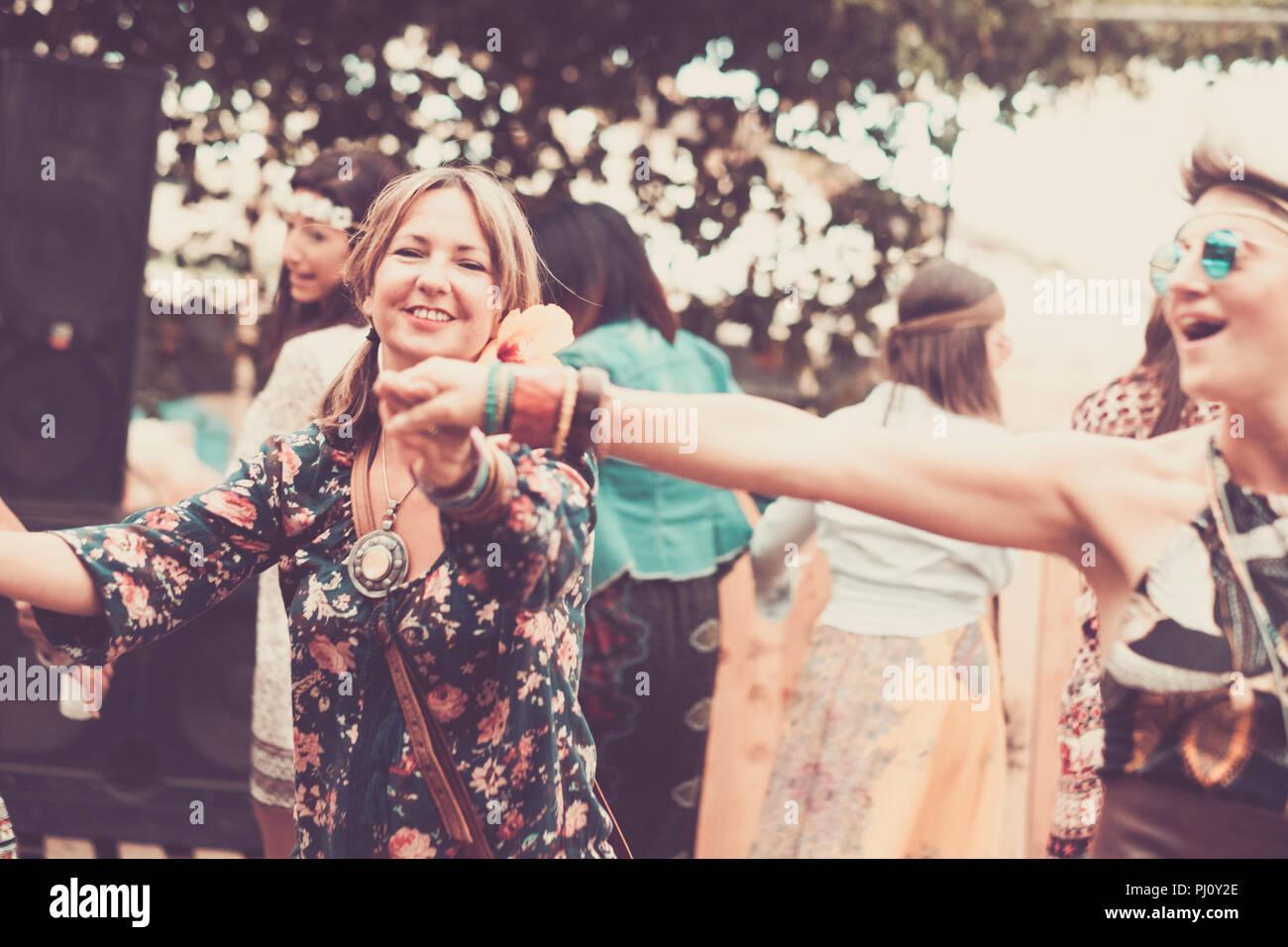 Giovani donne e ragazze in amicizia tutti insieme per celebrare e divertirsi in un bio luogo naturale. sorrisi e ridere per gruppo di hippies persone al Foto Stock