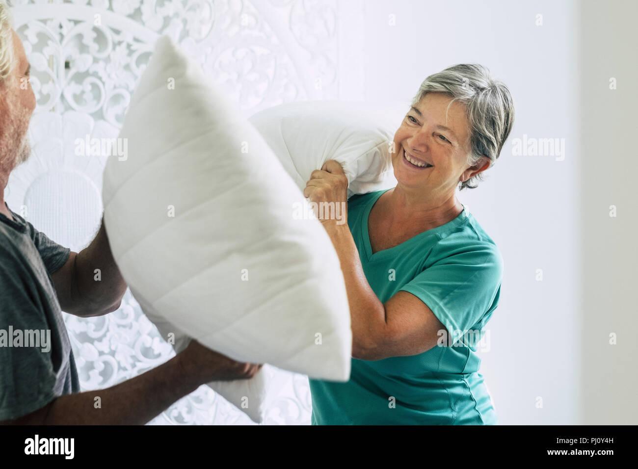Cuscini guerra in casa per la caucasian paio di giocoso senior adulto uomo e donna giocare in camera da letto al mattino. felicità e gioia insieme per sempre s Immagini Stock