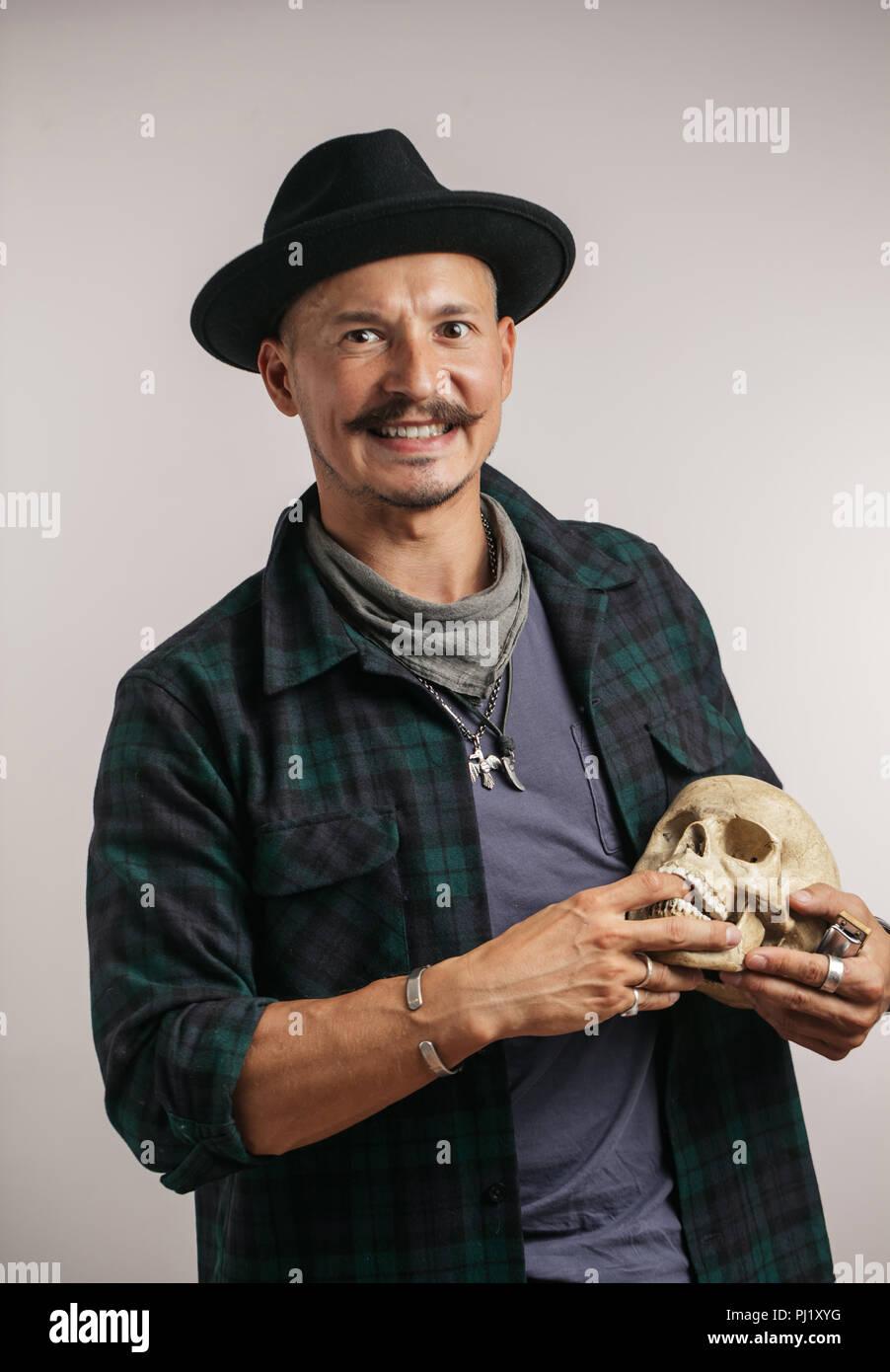 Elegante uomo con i baffi indossando un cappello e scull tenuta in posa in  ambienti interni c2e94b426ada