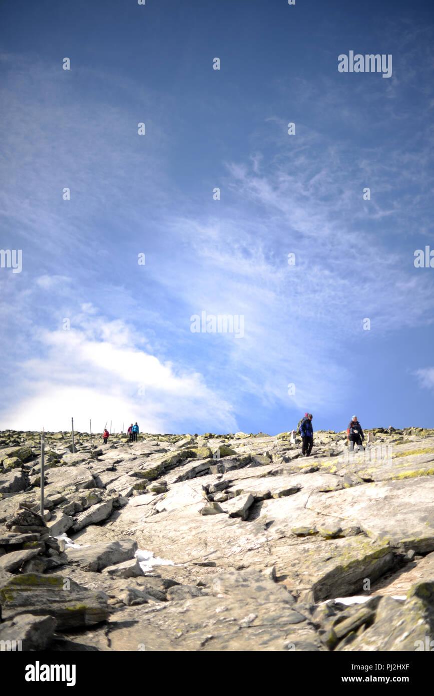 Persone di andare fino alla cima della montagna su una soleggiata giornata autunnale Immagini Stock
