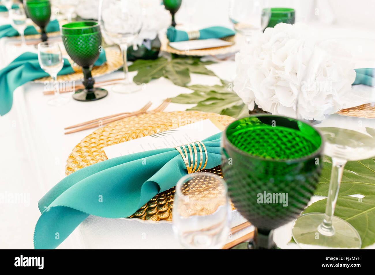 Interno della tenda per matrimonio diner, pronto per gli ospiti. Servita round table banchetti all'aperto nel tendone decorate i fiori delle ortensie, piatti d'oro e verde di tovaglioli. Concetto di ristorazione Immagini Stock